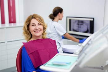 Woman smiling in dental chair wearing blue shirt