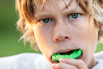 little boy in sports jersey putting in mouthguard