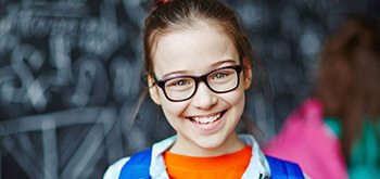 young girl with glasses smiling