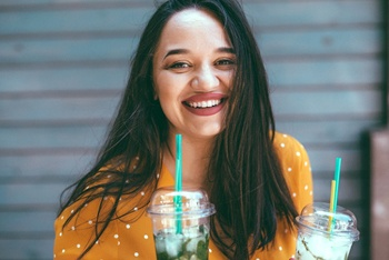 person smiling and holding two drinks