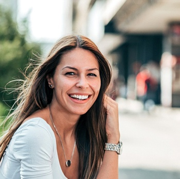 Woman with brown hair and white shirt smiling outside