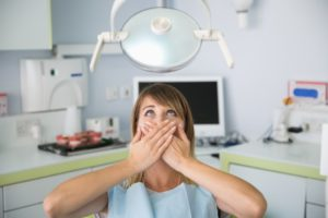 Woman covers her mouth because of dental anxiety in Bloomington